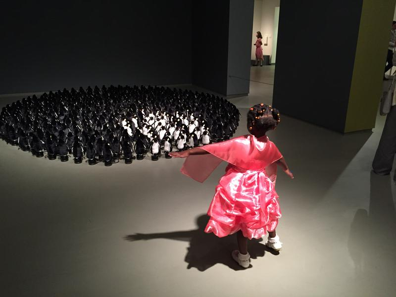 """A child interacts with """"Penguin Mirror"""" by Daniel Rozin."""
