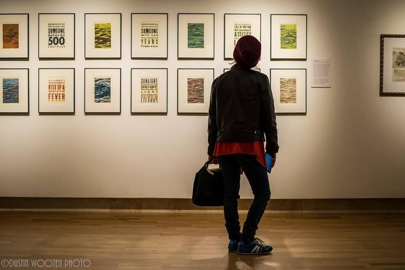person looking at paintings