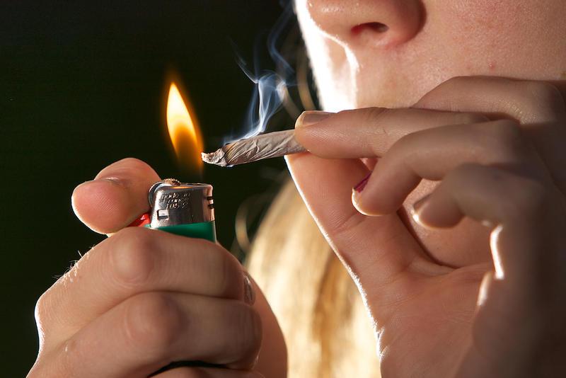 hand lighting marijuana joint