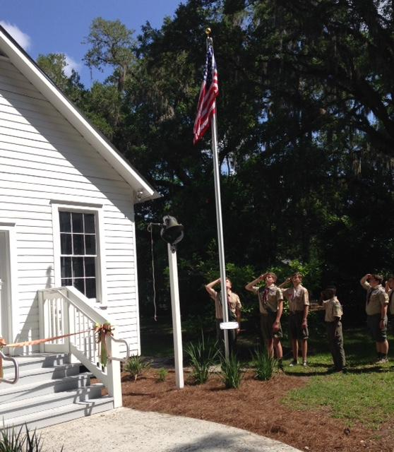 Boy Scouts Raise The US Flag In Front Of Schoolhouse Saturday