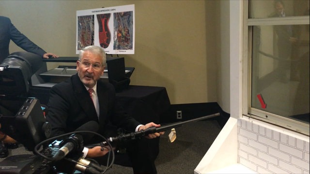 Assistant Attorney Mark Devereaux crouches down holding the rifle Richardson used in the attempted murder. He's demonstrating how he said the evidence proves Richardson acted the night he shot at Corrigan's head through a wall in his own home.