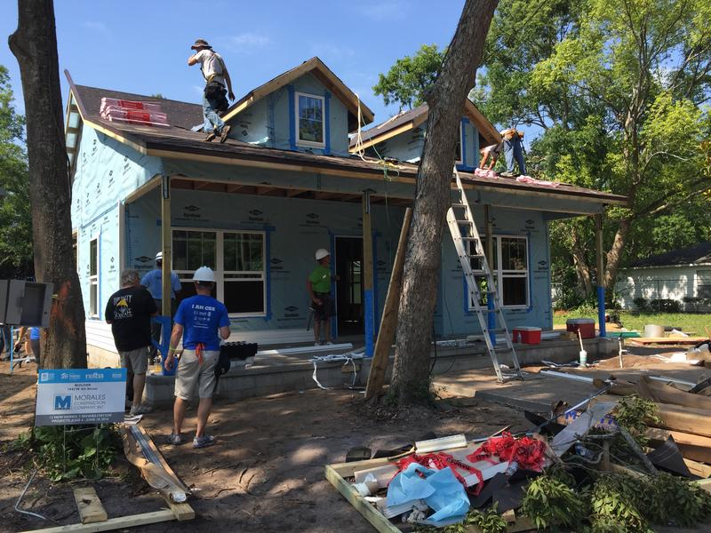 Volunteers put the finishing touches on the 2,000th home built by HabiJax.