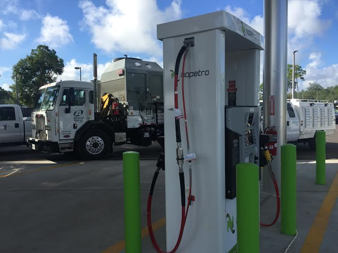 A fleet of natural gas vehicles parked behind new compressed natural gas pumps in St. Augustine.