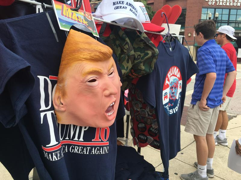 """Vendors sold  """"Make America Great Again"""" hats and Donald Trump masks in 90-degree weather before the Jacksonville Trump rally, Wednesday."""