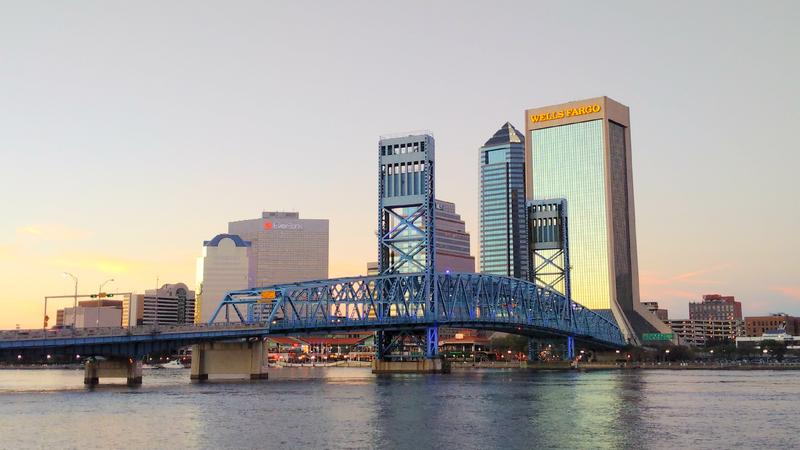 The Main Street Bridge is shown from across the St. Johns River. In the background is some of the Jacksonville skyline.