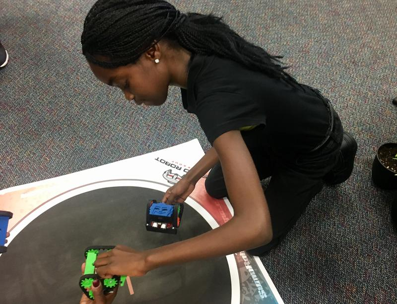 Northwestern sixth-grader Dalilah Josinvil was kneeling on the floor next to several small robots on wheels in her school's media center.