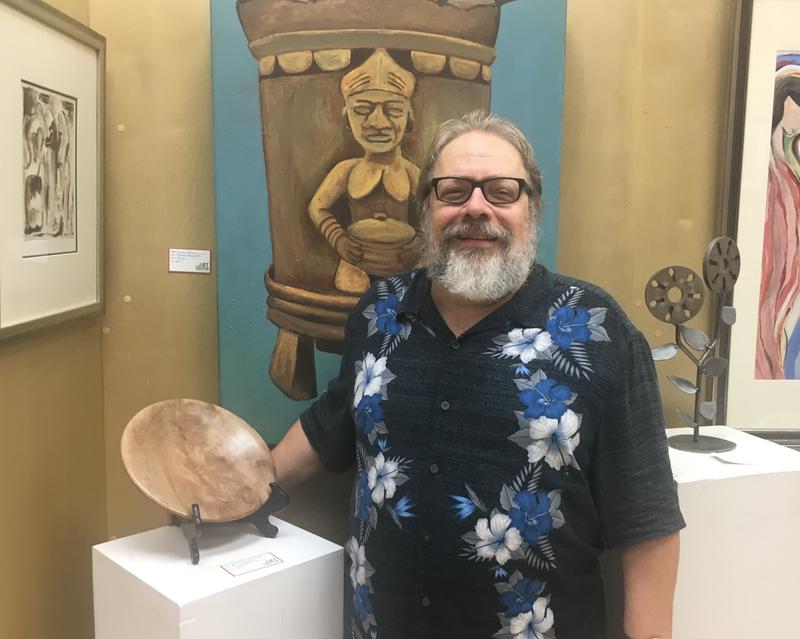 The Art Center's Cooperative board secretary Ed Malesky poses next to one of his wood pieces in The Landing's gallery Wednesday.