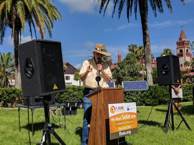 Compassionate St. Augustine's Warren Clark speaks at City Hall Tuesday in front of two large solar panels.