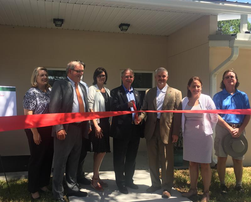 Congressman John Rutherford (center), surrounded by many involved in the Southern Villas project, gets ready to cut the ribbon for its grand re-opening.