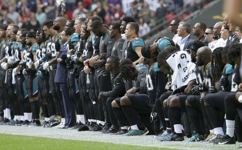 The Jacksonville Jaguars lock arms and kneel down during the playing of the U.S. national anthem in London on Sept. 24, 2017.