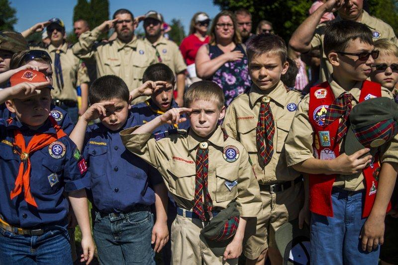 In this Monday, May 29, 2017 file photo, Boy Scouts and Cub Scouts salute during a Memorial Day ceremony in Linden, Mich.