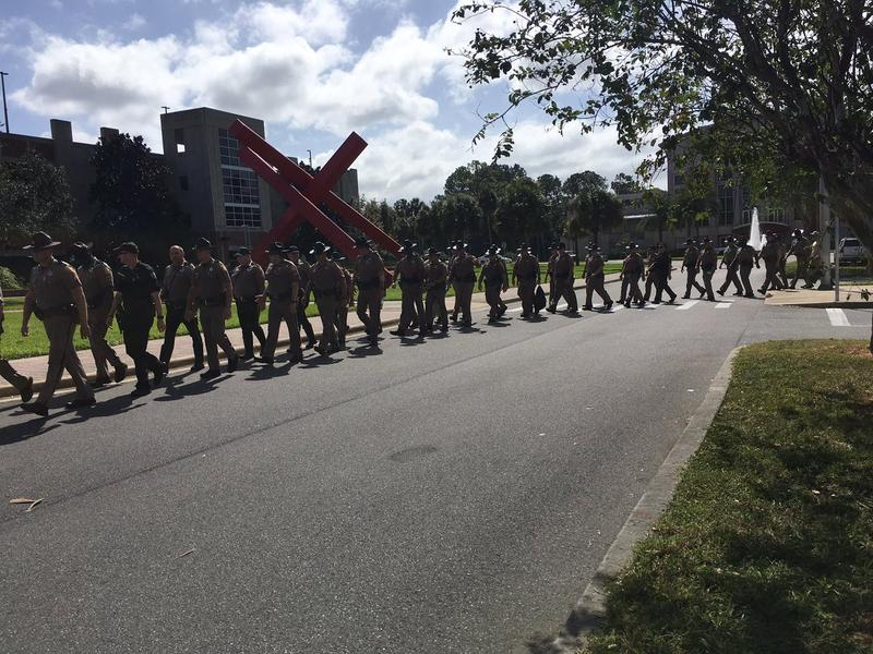 A line of law enforcement officcials are pictured outside the Philips Center at the University of Florida.