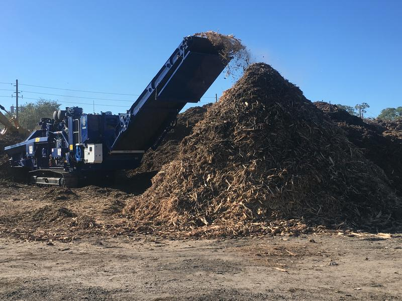 At a Jacksonville temporary debris collection site Thursday, backhoes were scooping debris from huge mounds and then depositing the scoops into a chipper that spits it out as mulch.