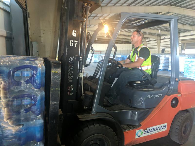 Crowley employee loads shipping container with water