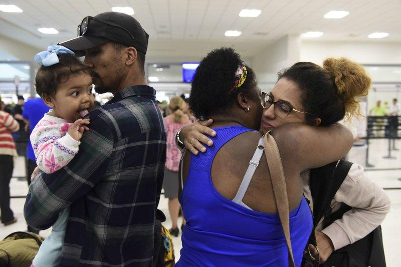 Waritza Alejandro embraces her mother-in-law Maritza Ortiz, before boarding a flight to Tampa with her husband Christian Vega and their daughter Tiana, in Carolina, Puerto Rico, Wednesday, Nov. 8, 2017. The couple lost their home to Hurricane Maria.
