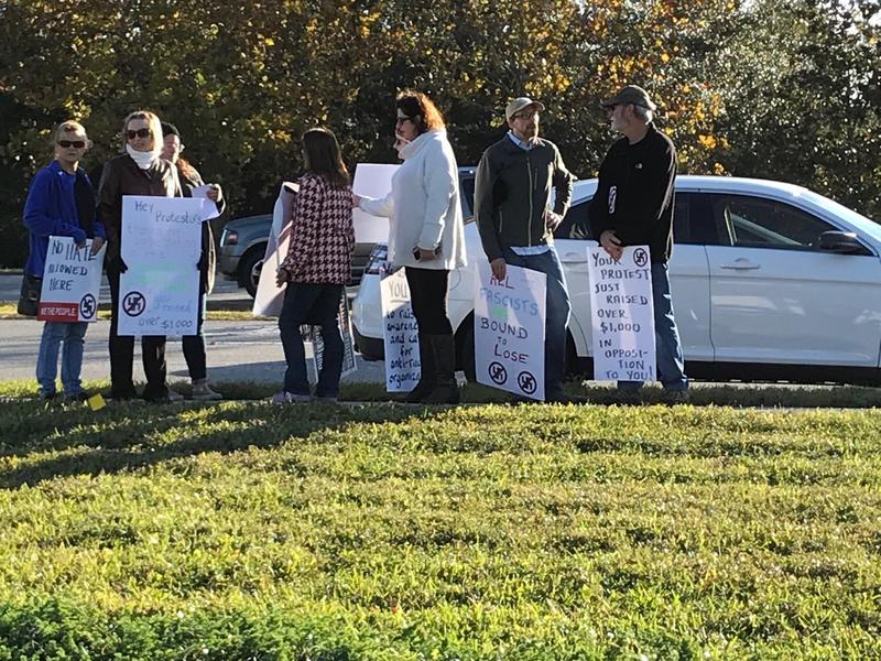 A small group of faculty is the first to show up outside UNF's Alumni Hall in support of the university.
