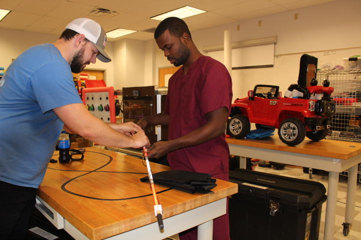 UNF engineering student Preston Loveday (left) and physical therapy student Darius Stukes work on a smart cane for Atlantic Coast High visually impaired students.
