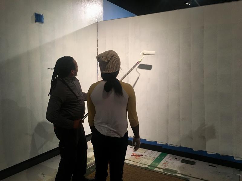 Ritz Museum archivist Yuwnus asami (left) and a volunteer paint the museum's walls Thursday.