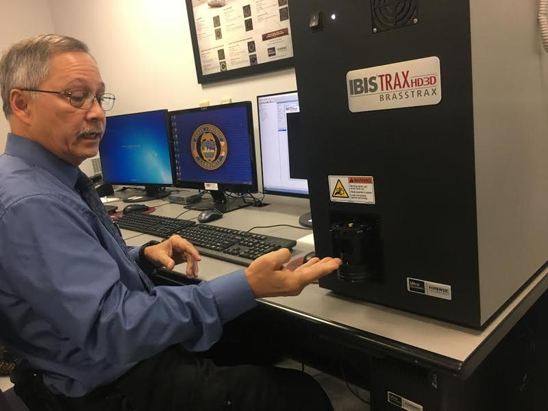Firearms laboratory manager Peter Lardizabal inserts a bullet casing into JSO's new IBIS machine.