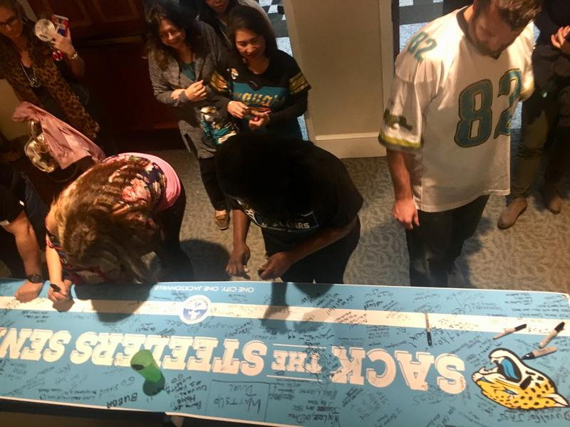 Fans lucky enough to get off work early signed a giant banner that the Jags will get on their way to Steel City Saturday.