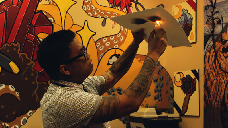 Fred Valdez Fajardo demonstrates a technique of shaping candle soot to form elaborate designs on paper.
