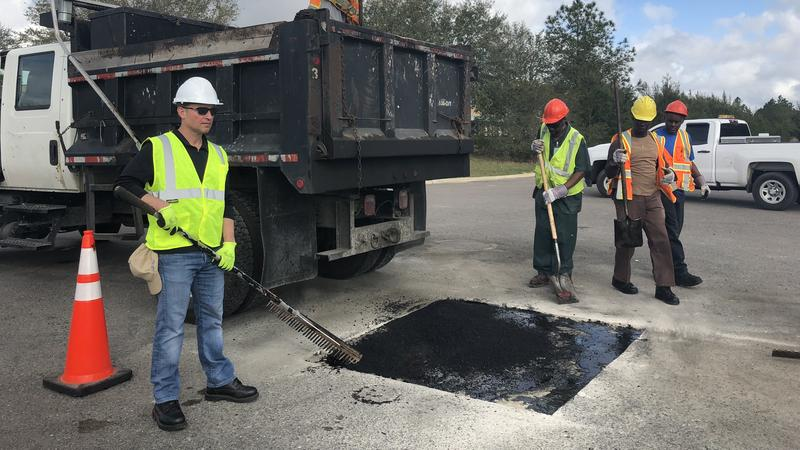 Mayor Lenny Curry helps patch a pothole on Whittaker Road Wednesday.