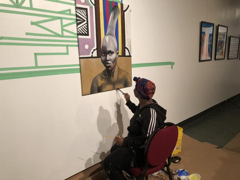 Yuzly Mathurin working on finishing touches on her painting.