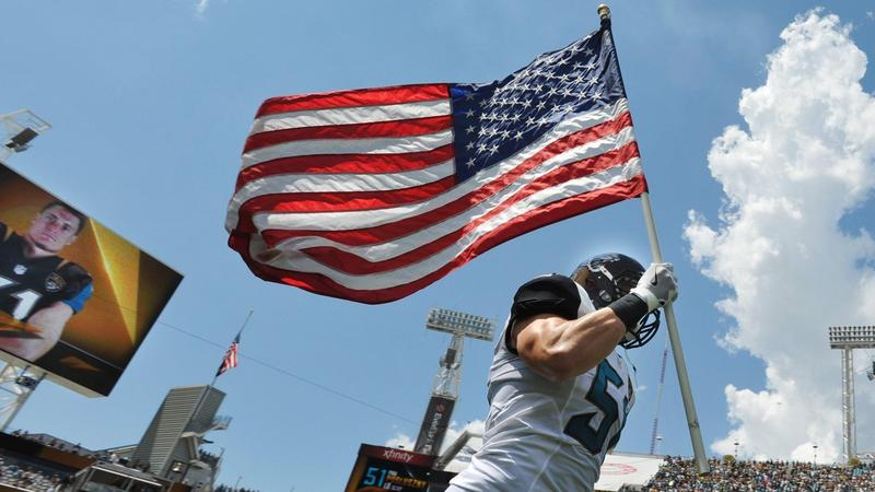Jaguars linebacker Paul Posluszny (51) carries the flag onto the field on Sept. 11, 2016 at EverBank Field.