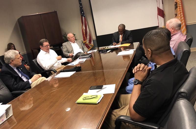 """Councilman Garrett Dennis leads a meeting with other council members, medical examiner's employees, and a Wolfson physician as they talk about """"hit-free zones."""""""