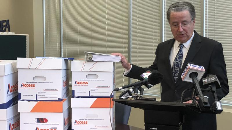 JEA CEO Paul McElroy shows the news media documents he presented to Jacksonville's City Council Thursday.