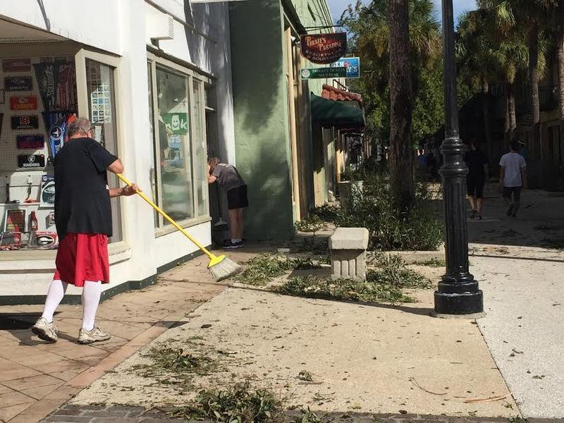 A man sweeps outside of his buisness after Hurricane Mathew passed.