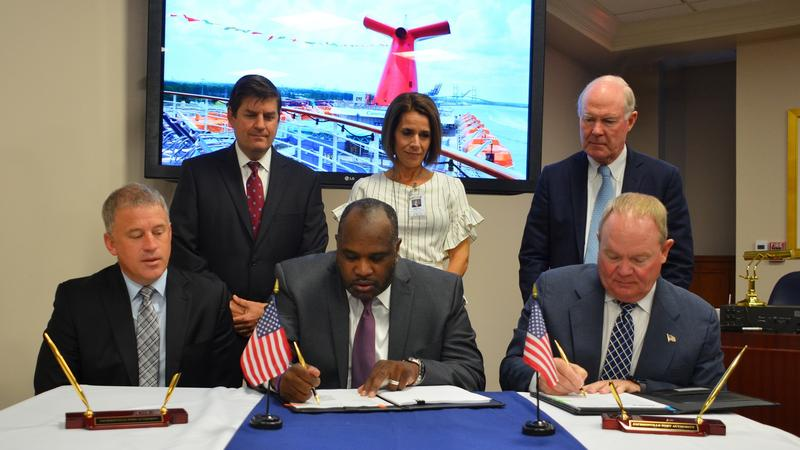 JAXPORT CEO Eric Green (center) signs a new agreement with Carnival Cruise LIne.