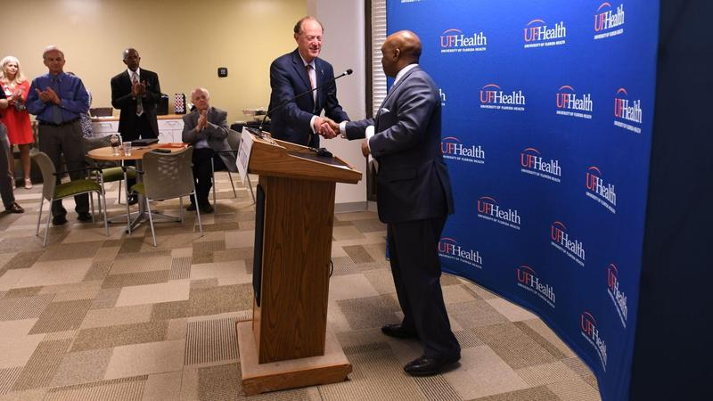 David Guzick, the UF's senior vice president for health affairs and the president of UF Health (left), shakes hands with Leon Haley, dean of the UF College of Medicine - Jacksonville and CEO of UF Health Jacksonville, during a press conference Friday .