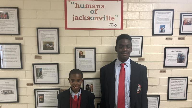 "Sixth-graders  Zavion Gibbs (left) and Deryc Plazz stand in front of their school's ""Humans of Jacksonville"" wall."