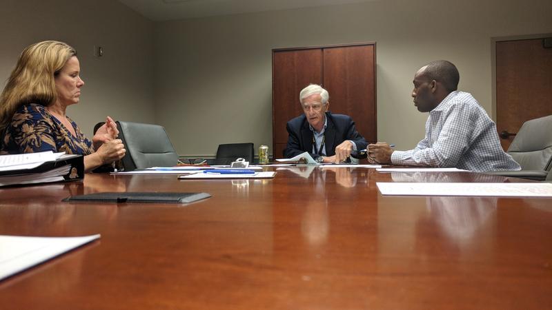Coouncilmen Bill Gulliford (center) and Garrett Dennis discuss the opioid trust fund Thursday.