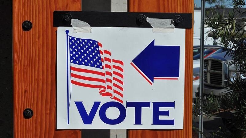 A sign located outside of a polling precinct, encouraging U.S. citizens to vote.