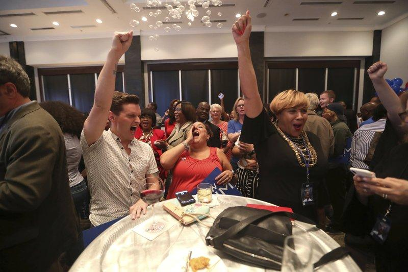 Tyler Clark, from left, Kara Weaver and Terri Lipsey Scott cheer on gubernatorial candidate Andrew Gillum during his watch party at Hotel Duval in downtown Tallahassee, Fla., Tuesday, Aug. 28, 2018.
