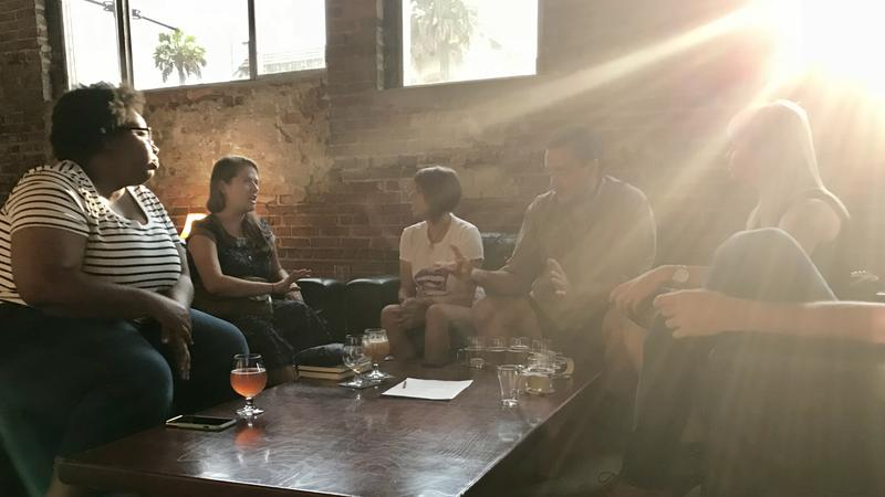 people sitting around table with beer