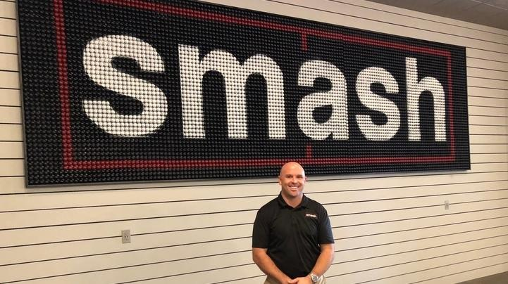 "Cathey standing in front of ""Smash"" sign."