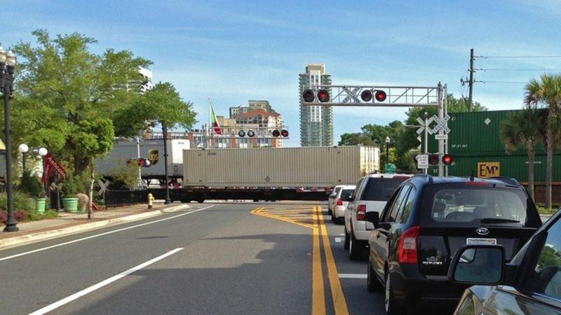 Cars line up behind a stopped train in San Marco.