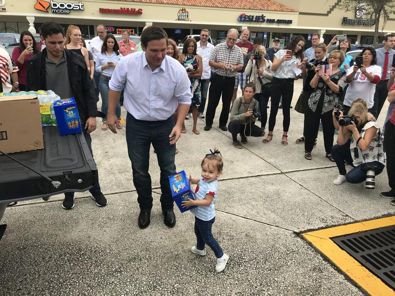Ron DeSantis and his daughter, Madison, help unload a truck filled with supplies as a crowd watches.