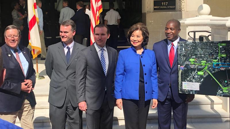 U.S. Transportation Secretary Elaine Chao is joined by local officials that included Mayor Lenny Curry (left of Chao) and JTA CEO Nathaniel Ford (right of Chao).