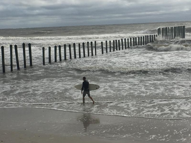 "A surfer walks along the shore at ""the poles"" at Hanna Park Beach in Jacksonville."