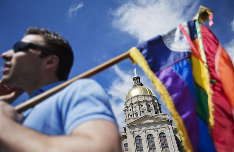 "In this March 17, 2015, file photo, the dome of the Capitol stands in the background as Stephen Saras, of Atlanta, holds a rainbow-colored flag during a rally against a contentious ""religious freedom"" bill in Atlanta."