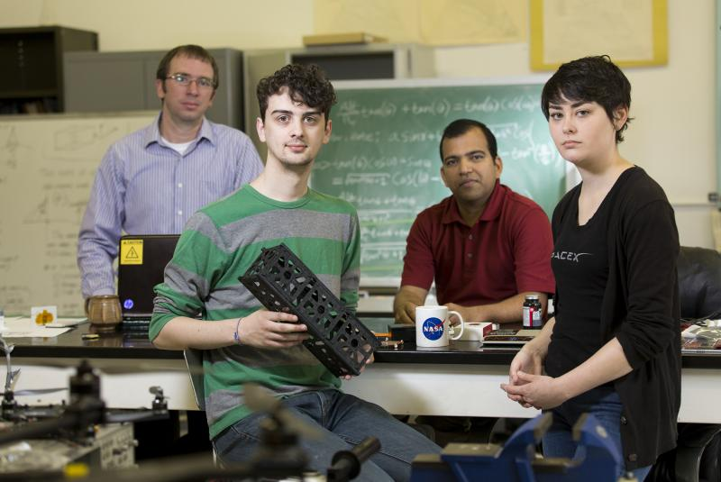 University of Georgia researcher David Cotten, student Caleb Adams, professor Deepak Mishra, and student Megan Le Corre are working with others at UGA to build two cube satellites into space. Adams holds a 3-D printer model of the CubeSat.