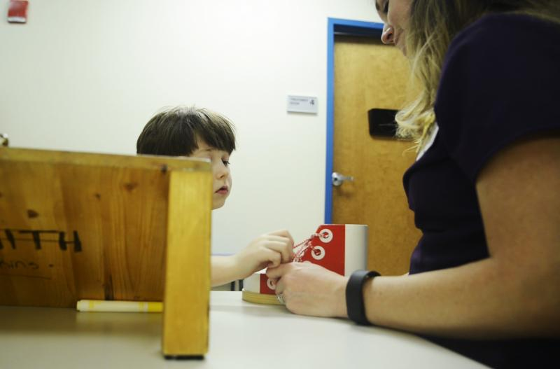Alex Rayburn, seven,  practices tying and untying a shoe with the help of physical therapist Kathryn Staples at the Autism Center at Navicent Health in Macon.