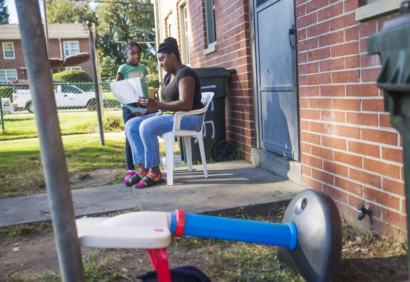 Lashonda Hill helps one of her children with homework outside their apartment in the Tindall Heights Housing Project in Macon. Hill was among a number of women in the neighborhood who hoped that the coming demolition of the projects would mean a shot at m