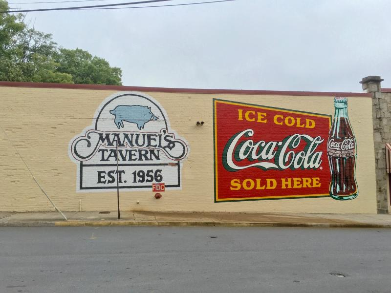 The newly-repainted signs advertising Manuel's Tavern and Coca-Cola.
