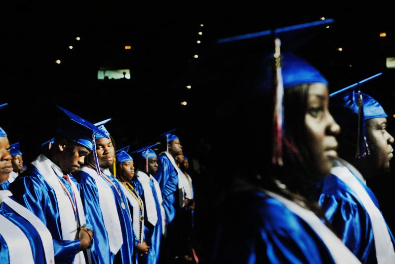 Deandre May, second from left, straightens a cord marking one of his graduation honors as friend Peter McKenzie, third from left, looks on during Southwest Macon High School graduation ceremonies in 2009.