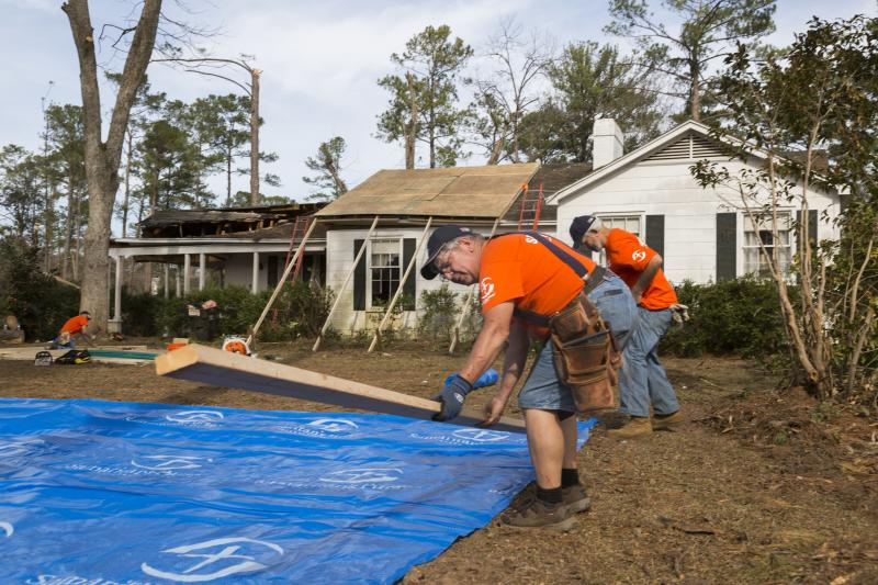 Volunteers with Samaritan's Purse, a disaster relief group associated with Franklin Graham Ministries, work on securing a storm damaged roof with a tarpaulin in Albany, Ga.